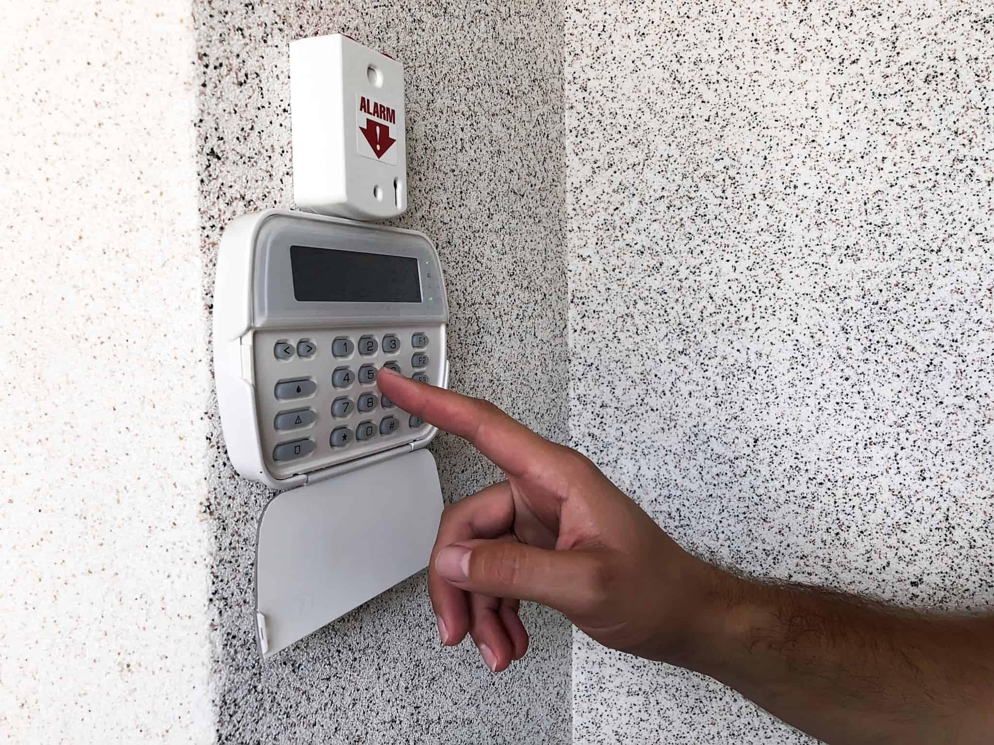 pessoa a colocar o alarme de casa ao digitar numeros