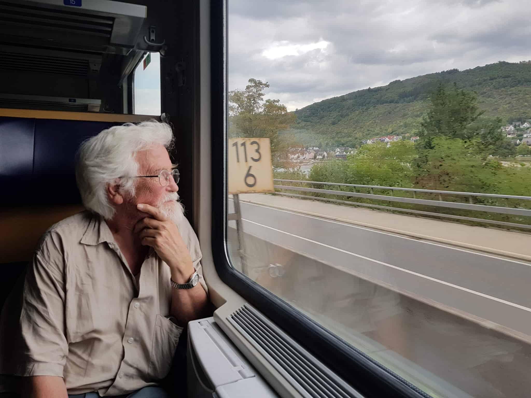 pessoa mais velha de cabelo branco a olhar para a janela dentro de um comboio