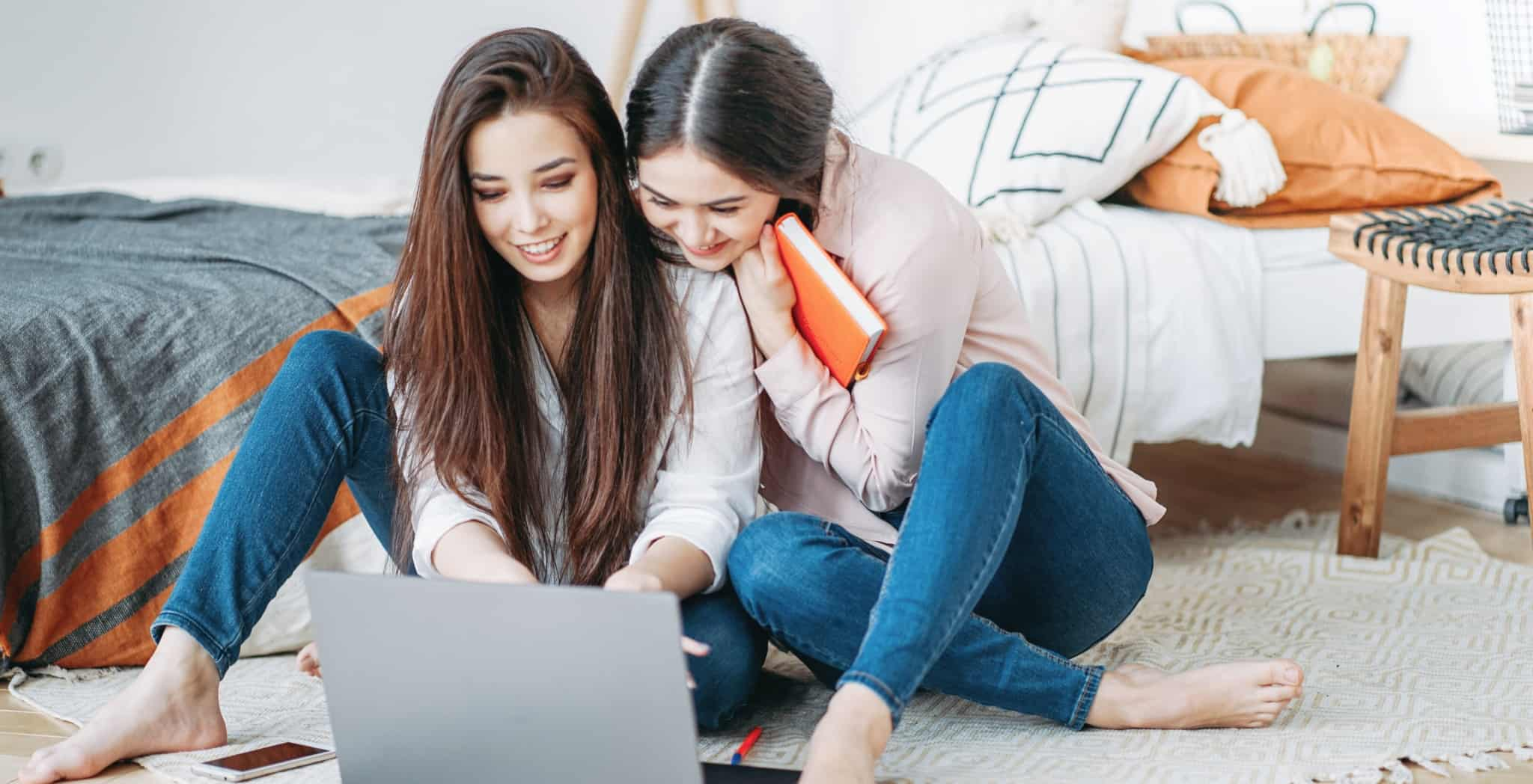 Duas raparigas em casa a trabalhar com o computador