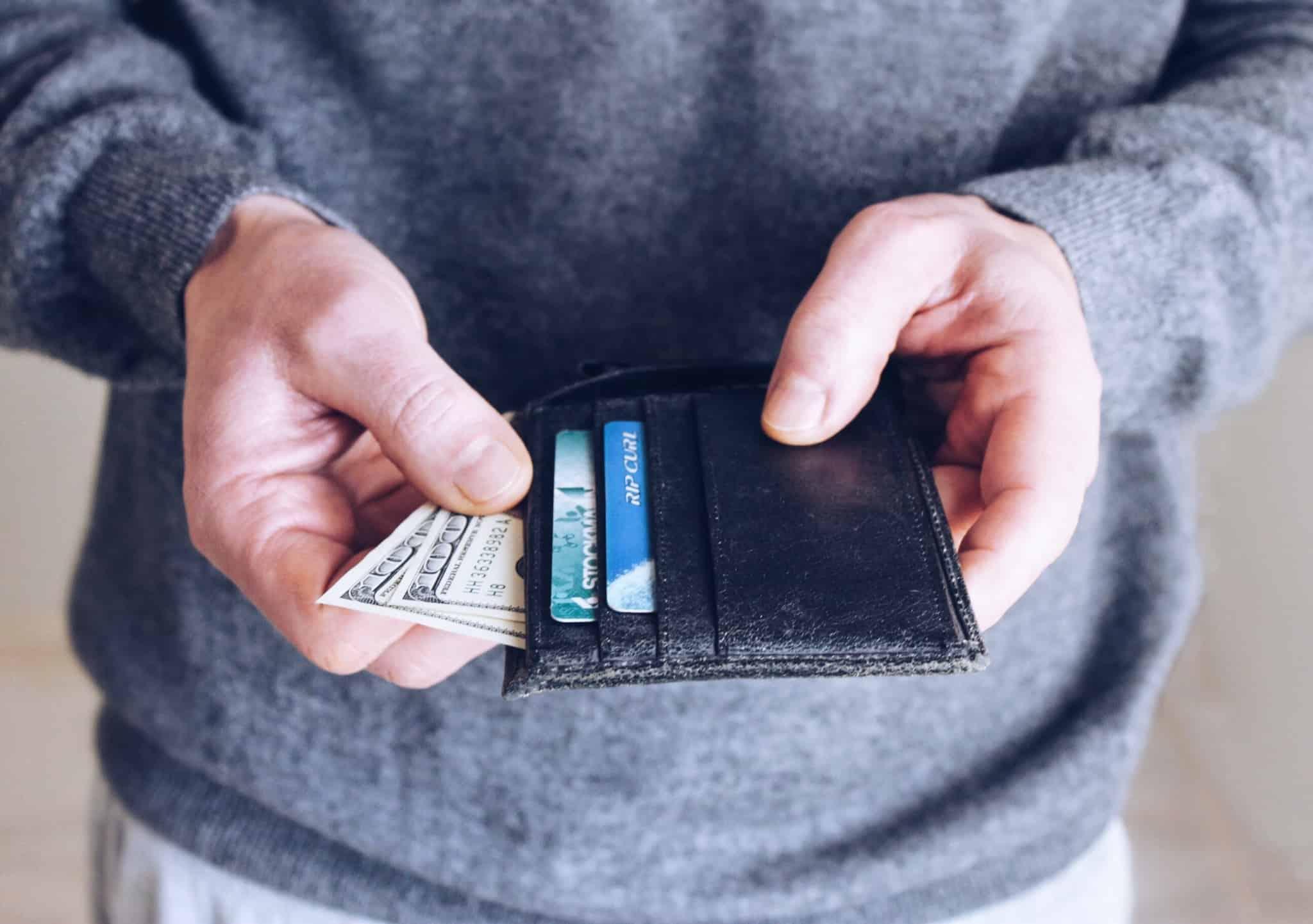 pessoa a mexer na carteira com cartões e notas