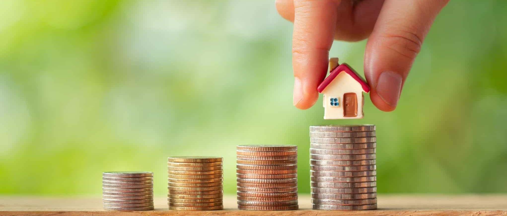 mão a colocar uma casa miniatura numa pilha de moedas
