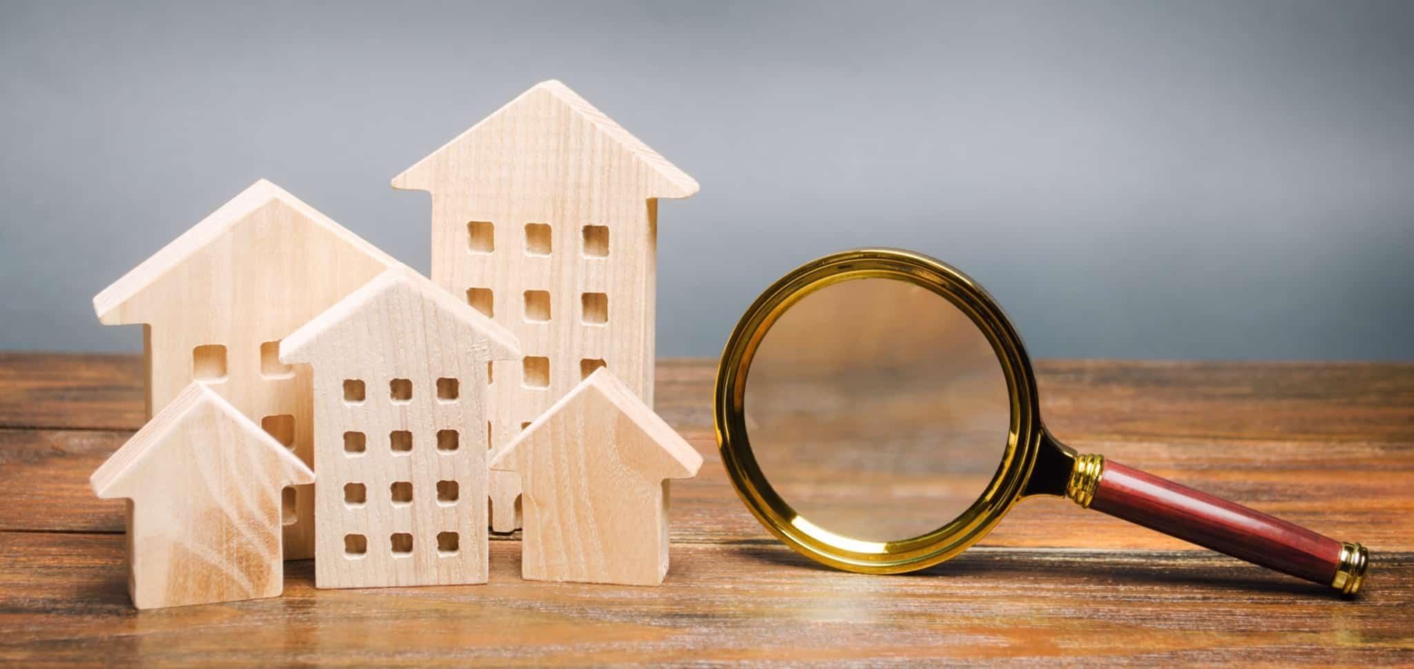 Figuras de casas e prédios em madeira ao lado uma lupa