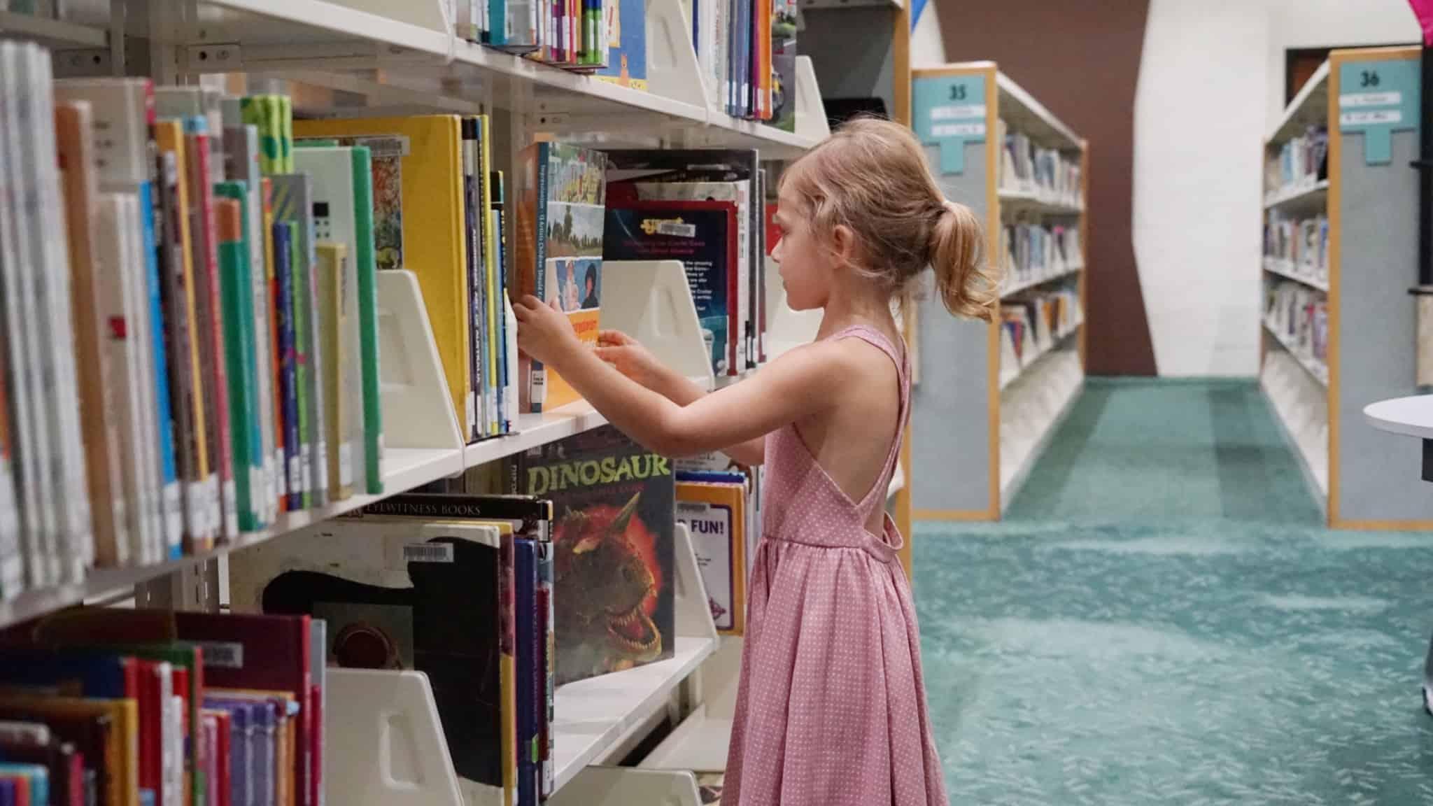 rapariga loira na biblioteca a ver livros