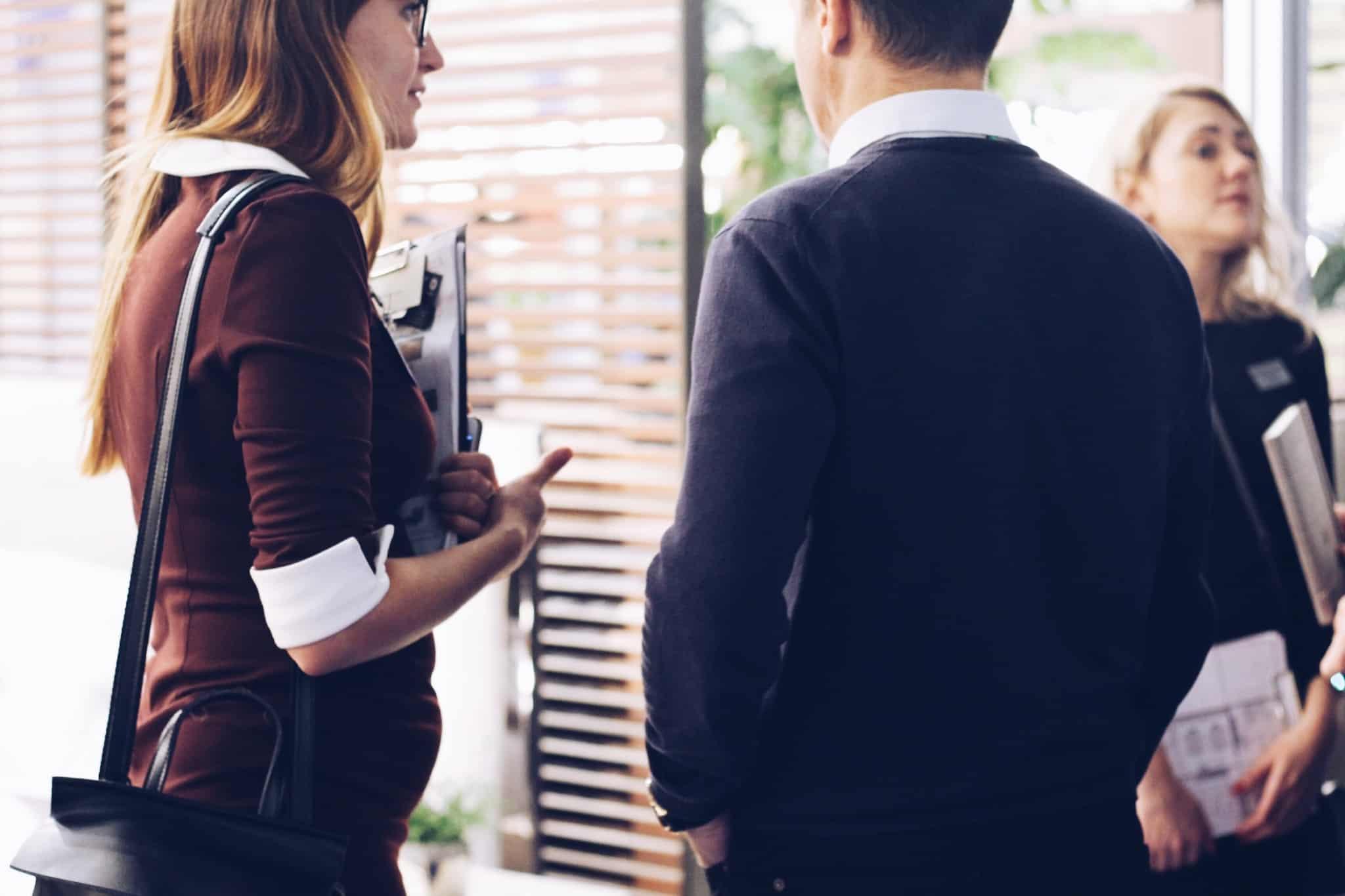 dois colegas de trabalho a conversar à porta de uma sala