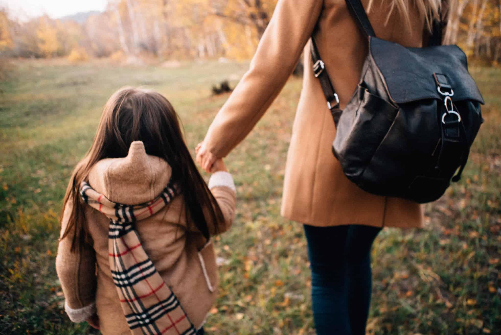 mãe e filha vestidas de beje a passear no parque no outuno