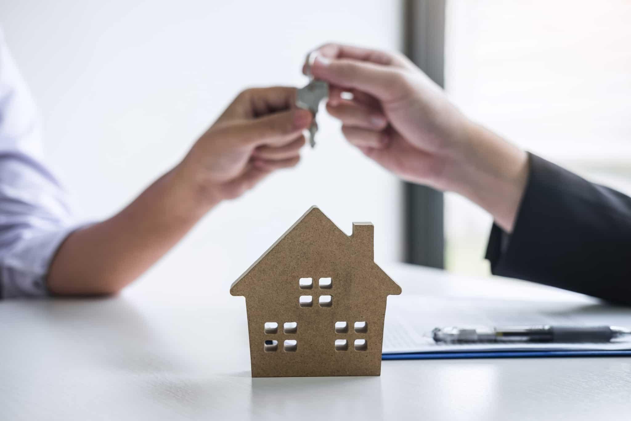 agente imobiliário a dar chave de casa a um cliente com camisa branca