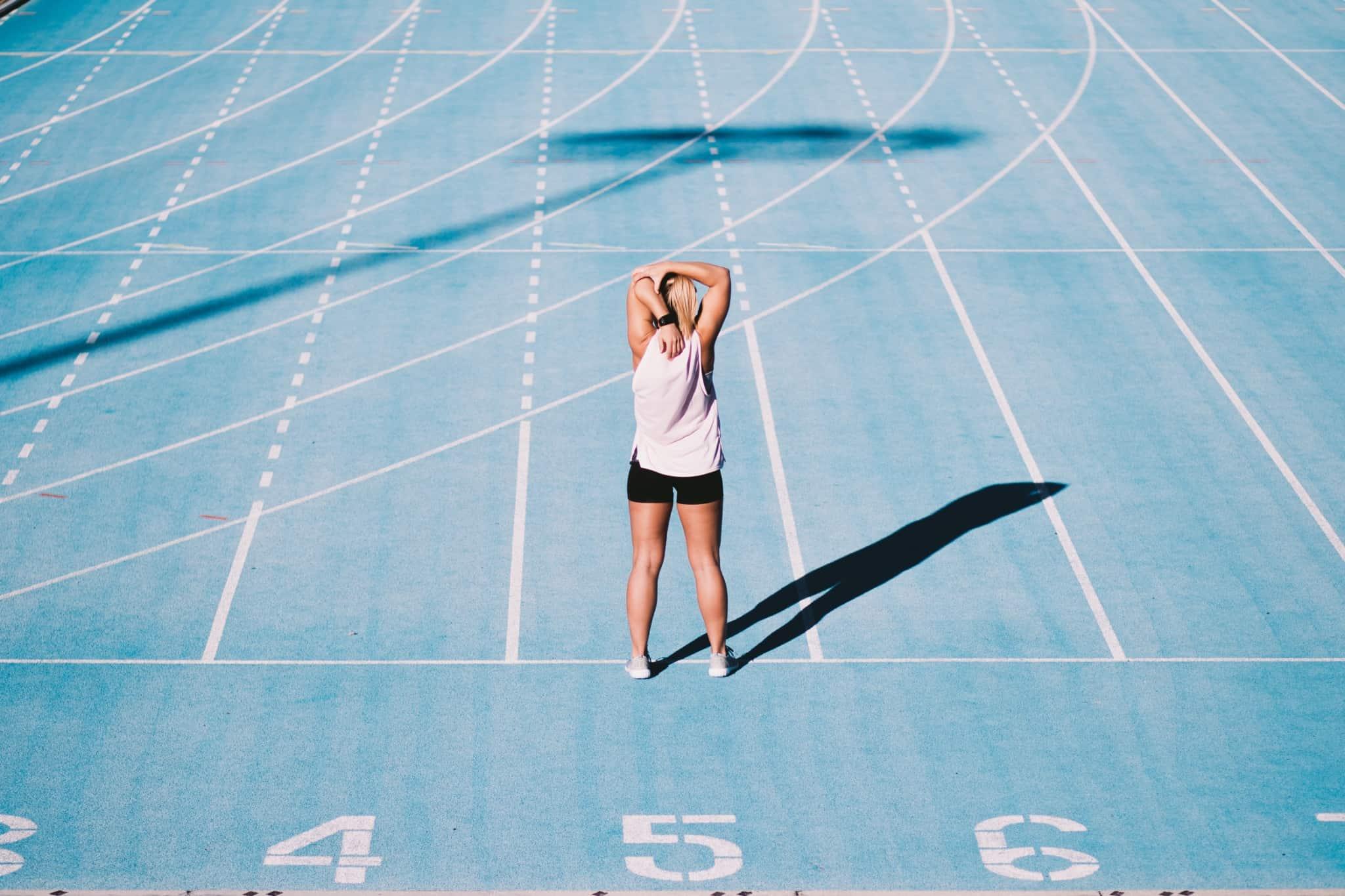 mulher desportista a alongar as costas numa pista de corrida azul