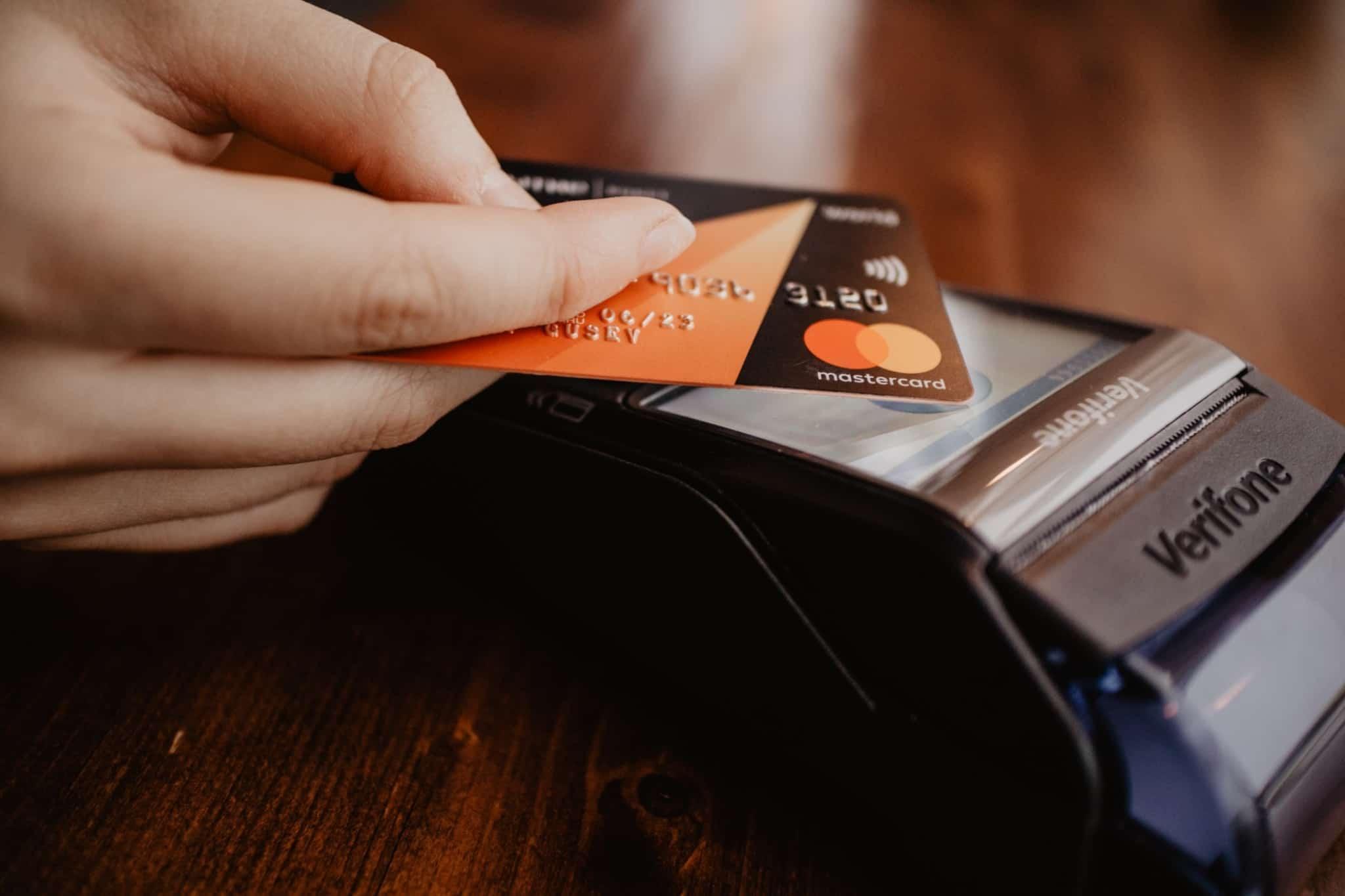 pessoa com um cartao preto da mastercard a fazer uma compra no terminal de pagamento