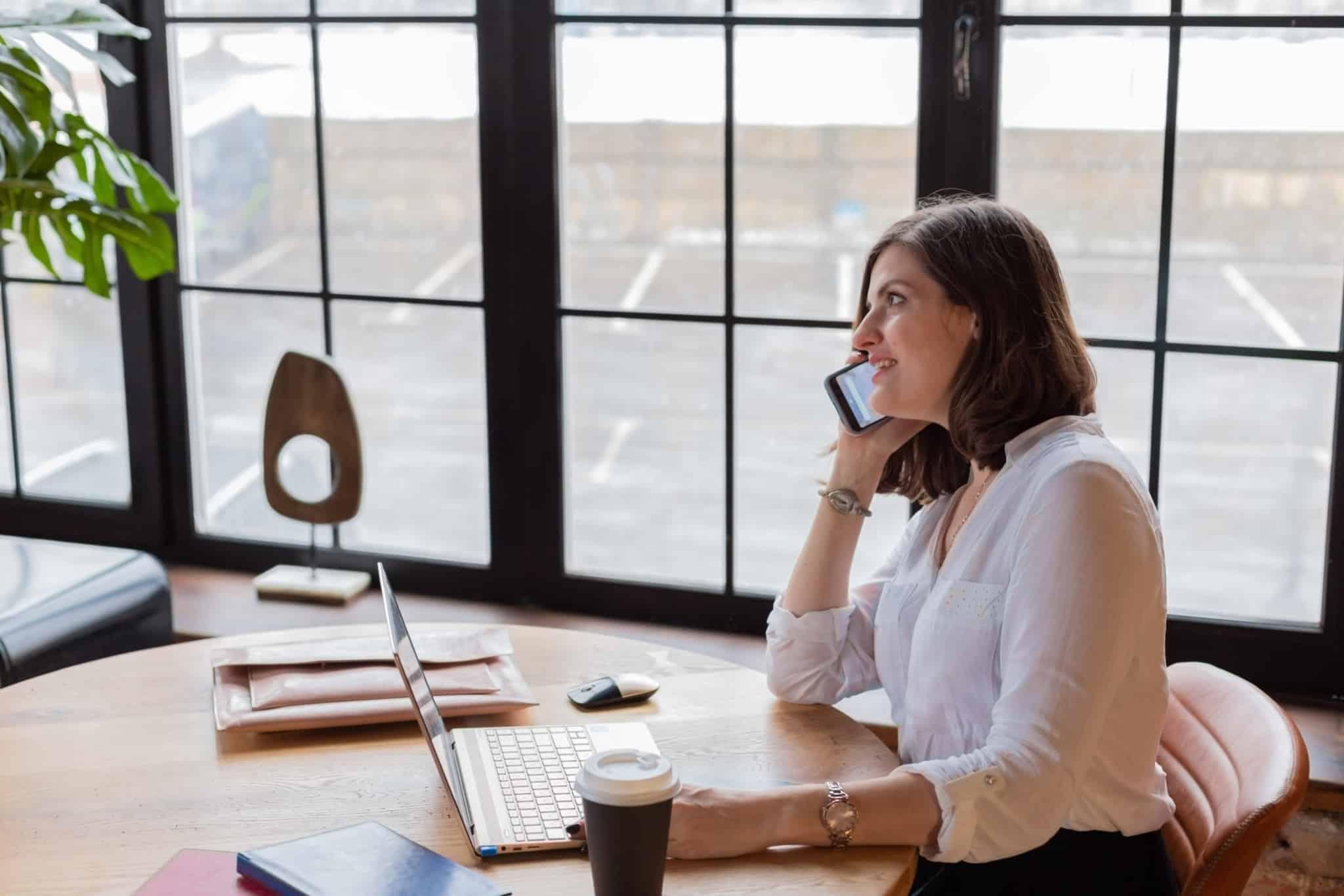 mulher a falar ao telefone e a trabalhar