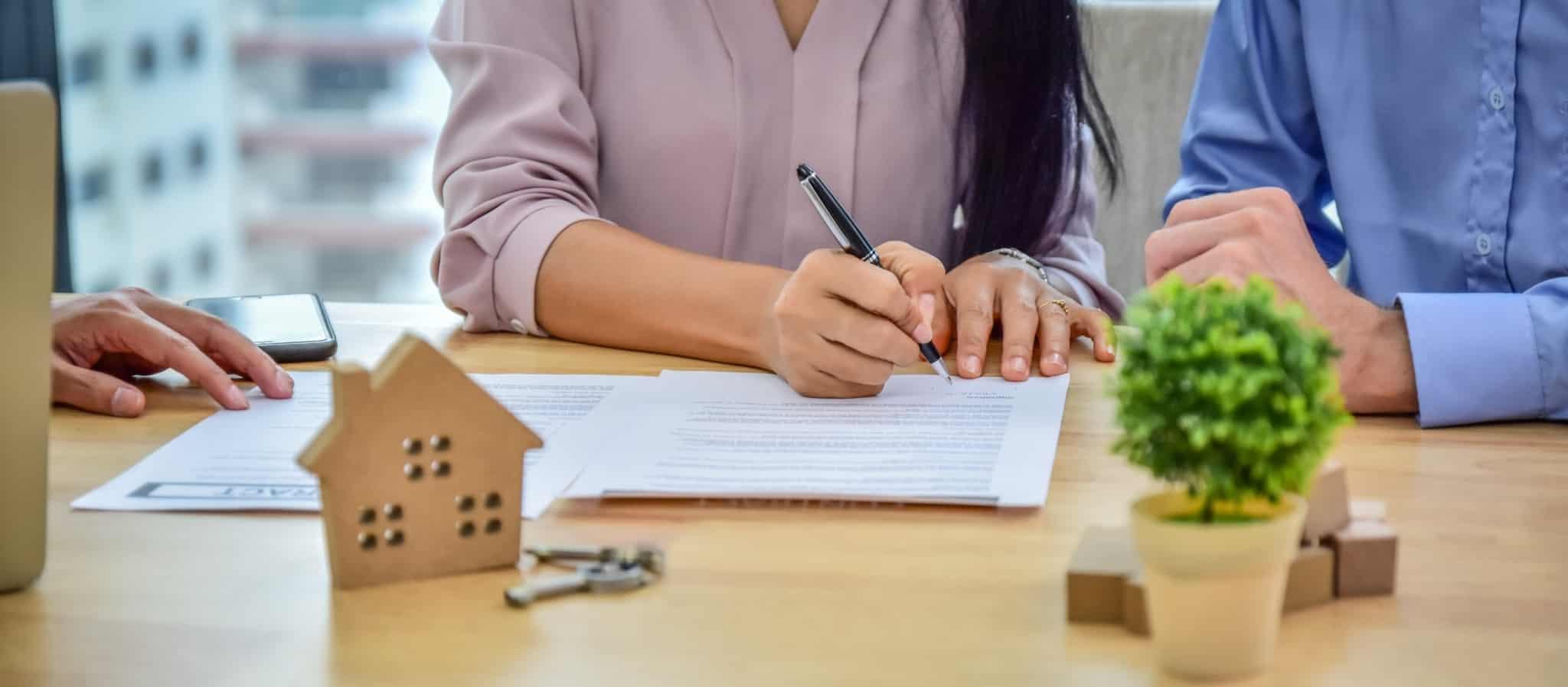mulher e homem a assinarem contrato casa