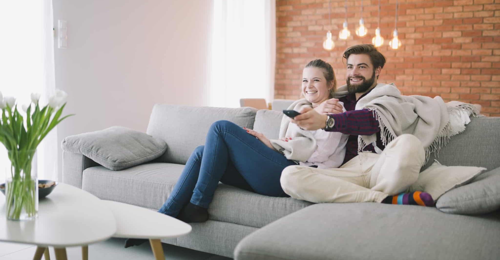 Casal sentado no sofá a ver televisão