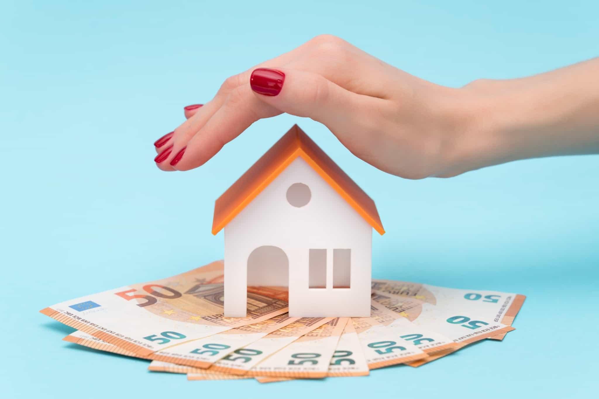 Miniatura de uma casa sobre várias notas de 50 euros e uma mão de mulher por cima