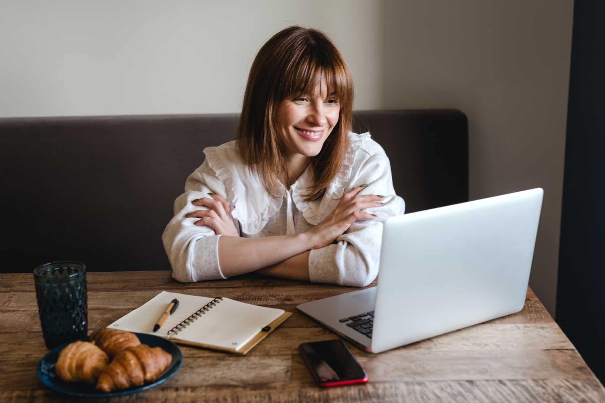 Mulher a trabalhar a partir de casa, sentada a uma mesa de trabalho em frente ao computador