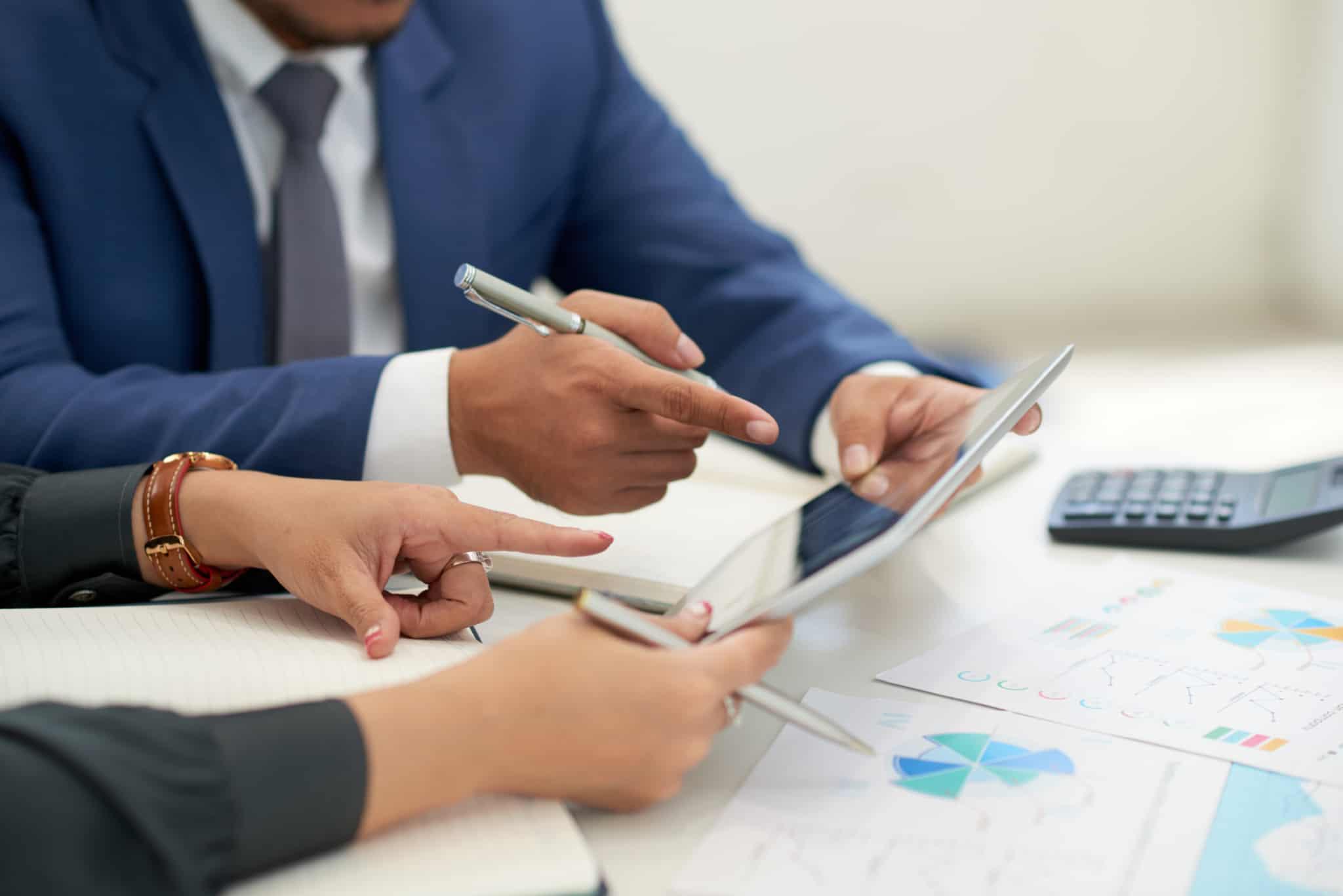 mãos de duas pessoas sentadas numa secretária a analisar folhas e um tablet