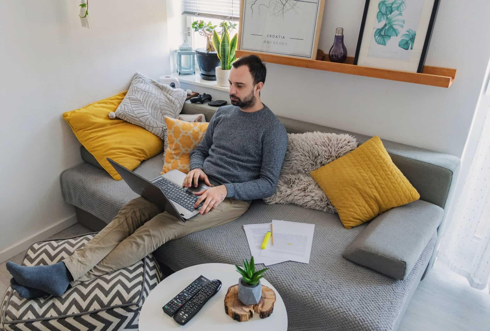 Homem sentado no sofá a trabalhar com o seu portátil em cima das pernas