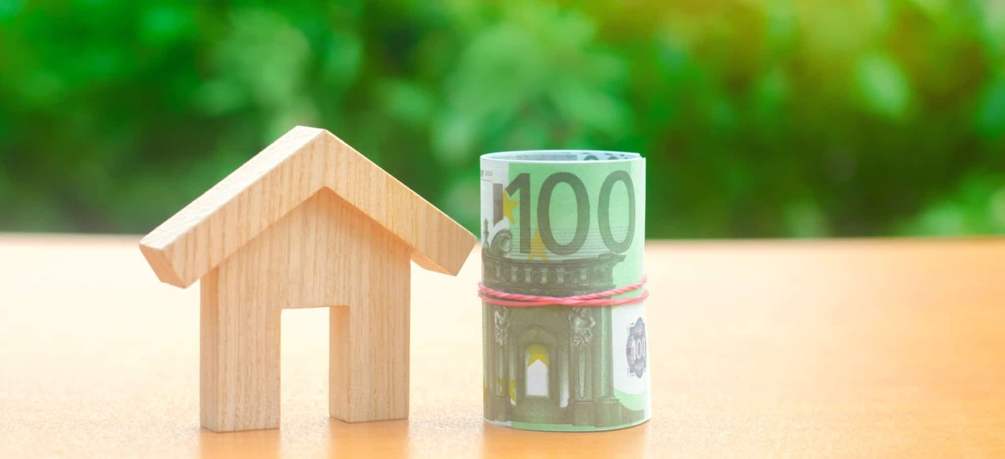 Miniatura de uma casa em madeira ao lado de um rolo de notas de 100 euros