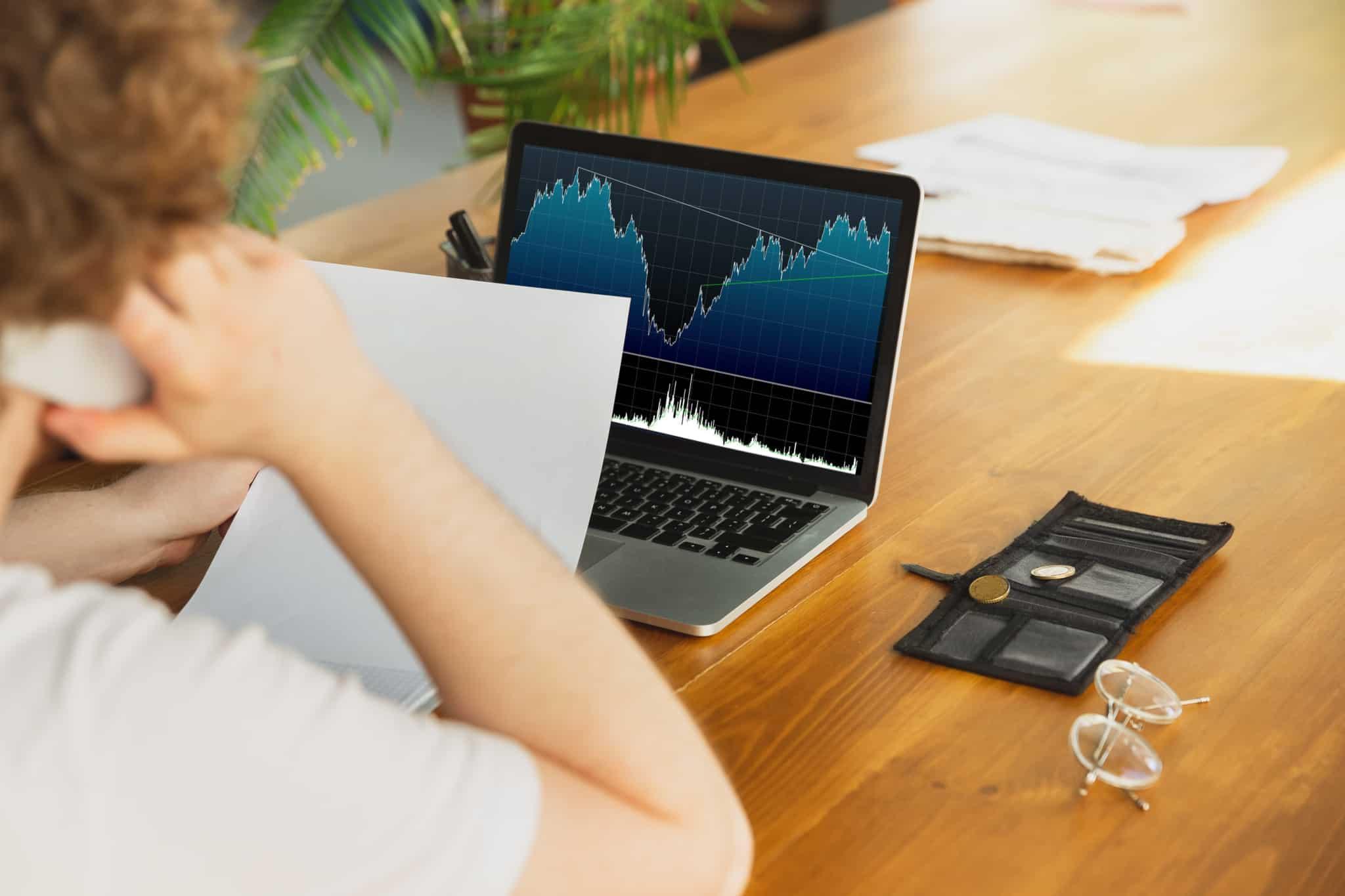 Homem ao telefone enquanto analisa o desempenho dos seus investimentos, através de uma folha e de um gráfico no computador