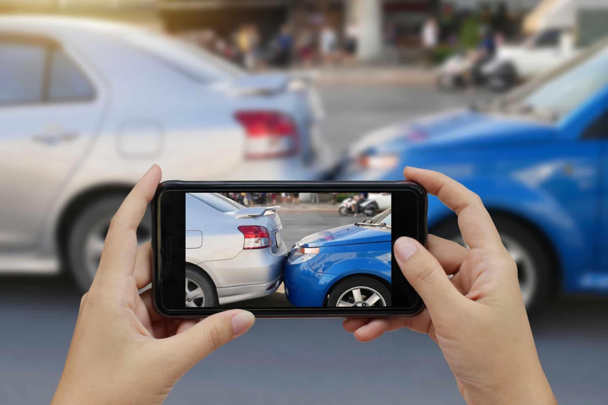 Pessoa tira fotografia com o seu telemóvel a um acidente entre carros