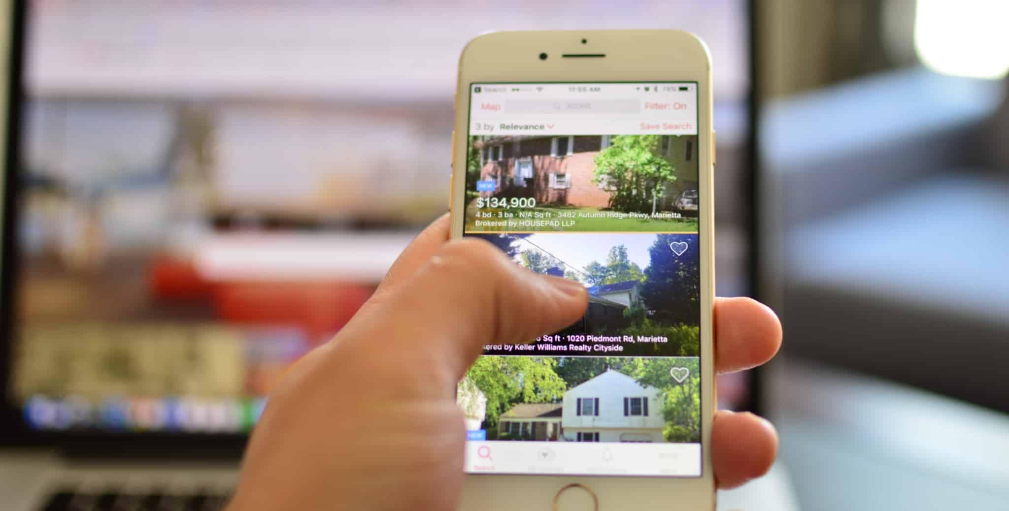 pessoa a pesquisar no telemóvel casa no website de vende casas