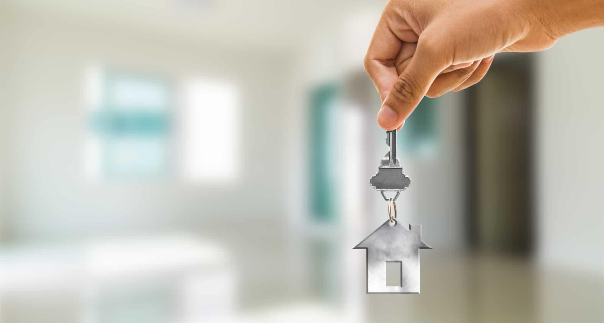 Mão a segurar um porta-chaves em forma de casa