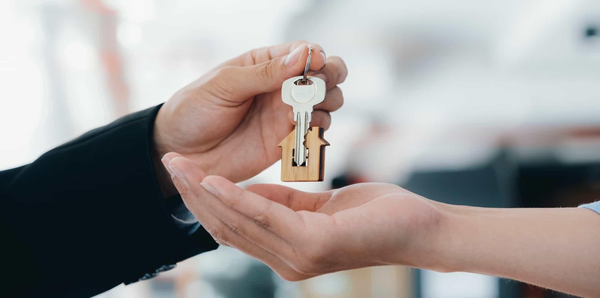 Uma pessoa a dar uma chave de uma casa a outra