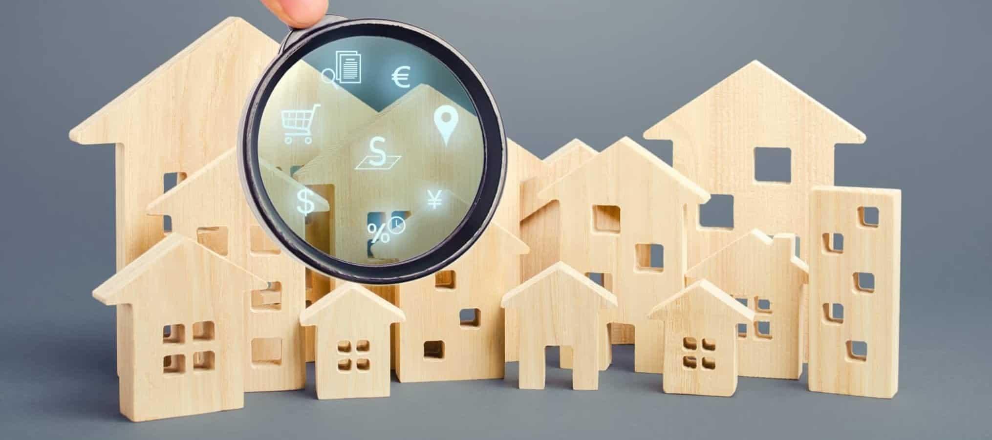 Figuras de casas e prédios em madeira e uma lupa à frente através da qual se veem simbolos de dinheiro, localização e compras