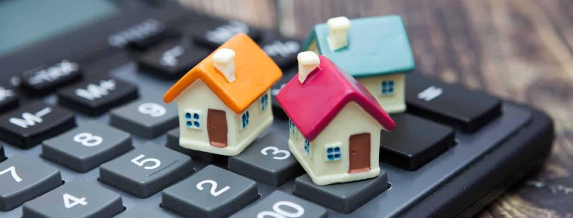 figuras de casas em miniatura em cima de uma máquina de calcular