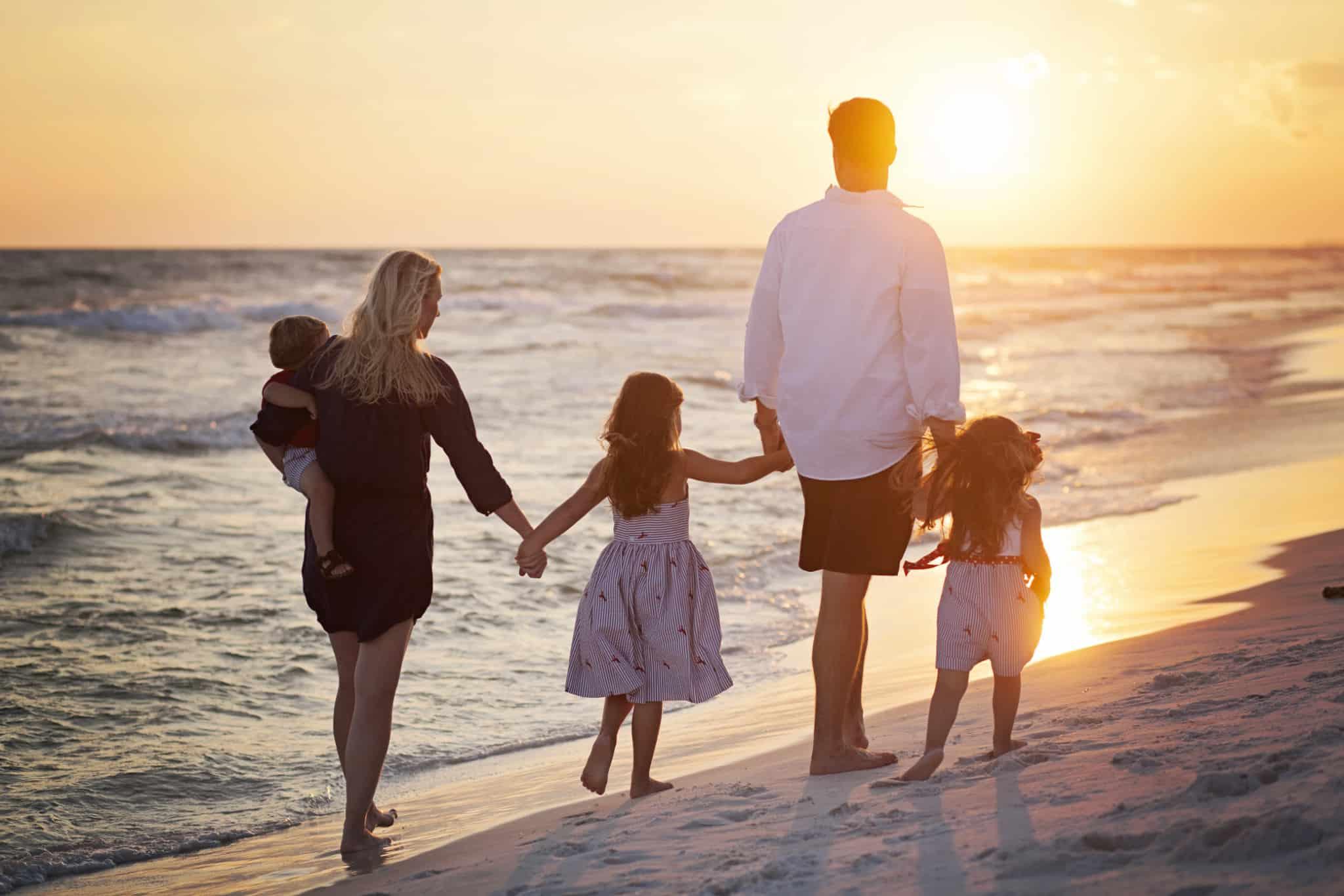 Família (casal de adultos mais três crianças) a passear na praia à beira mar