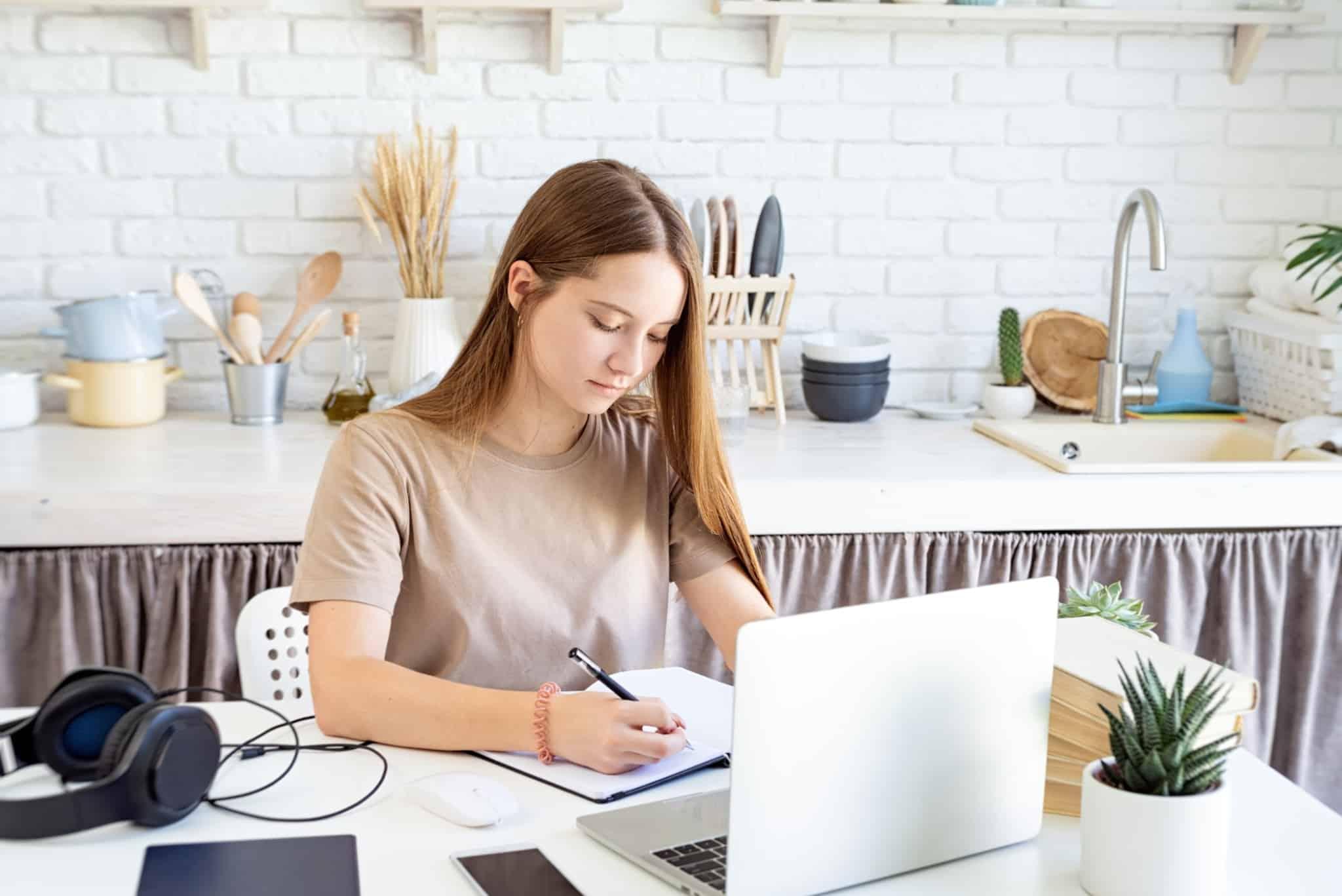 jovem mulher consulta o seu computador na mesa da cozinha