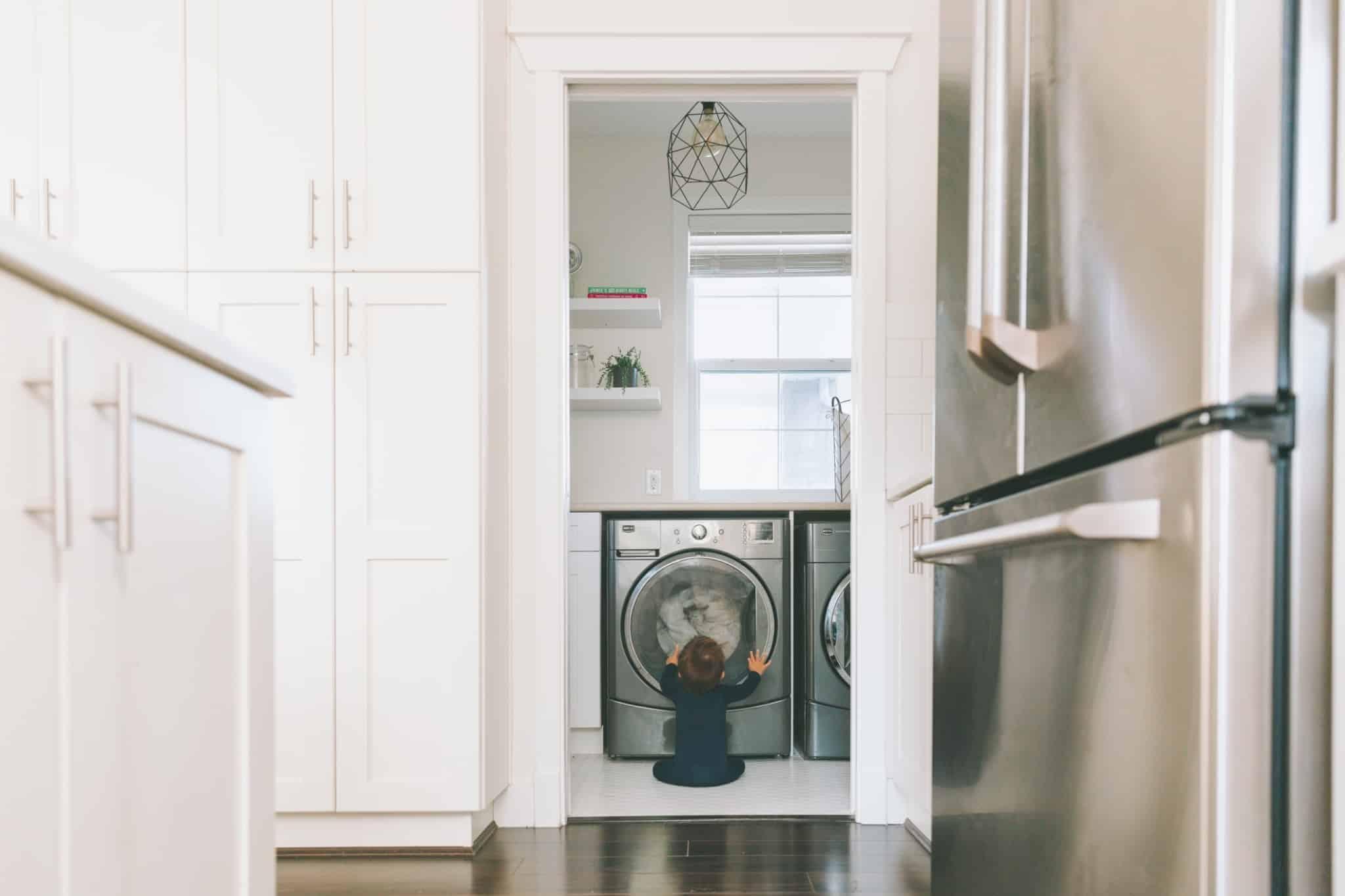 Criança sentada no chão a ver a máquina de lavar roupa a funcionar