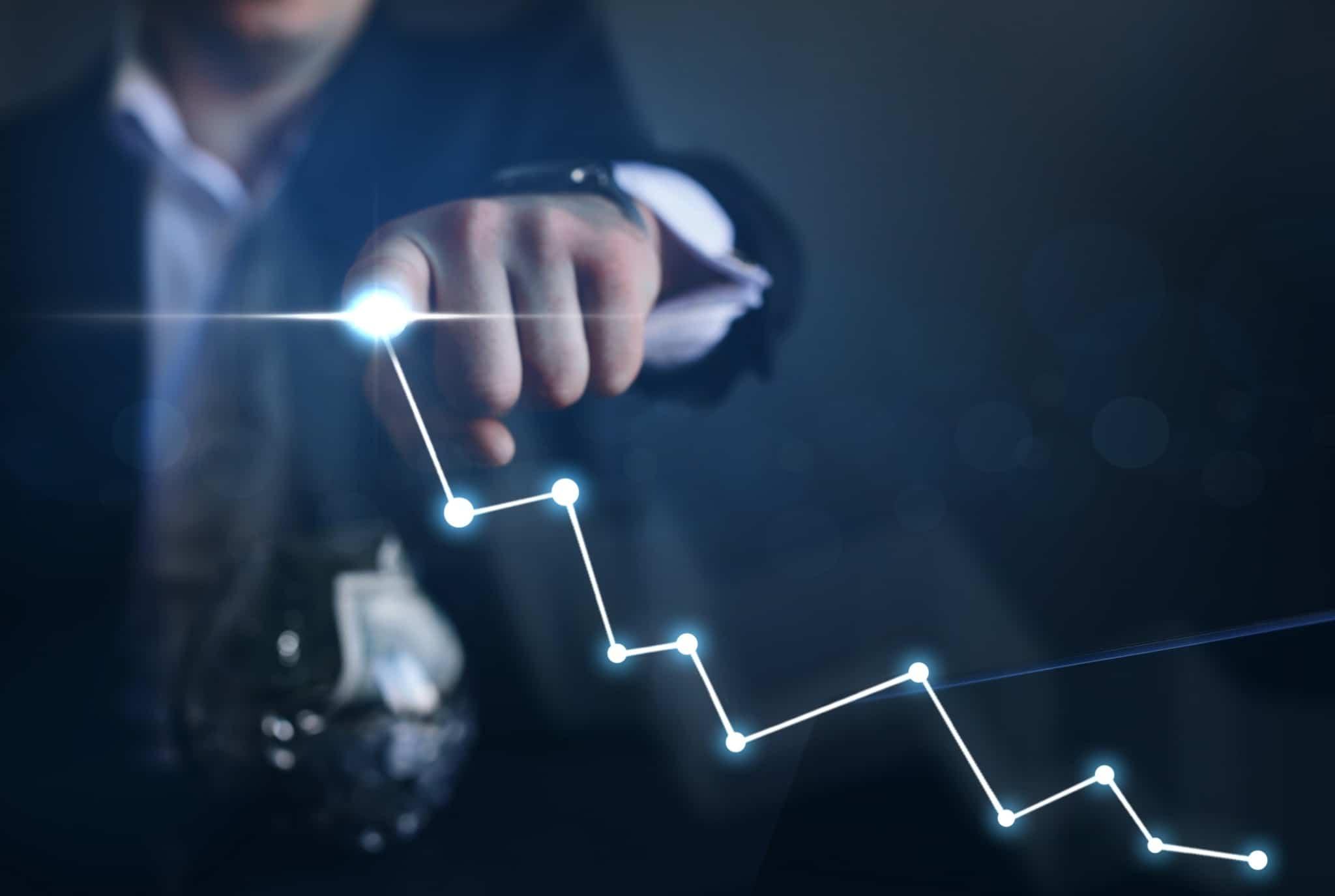 Mão de homem desenha um gráfico, mostrando o desempenho de um investimento