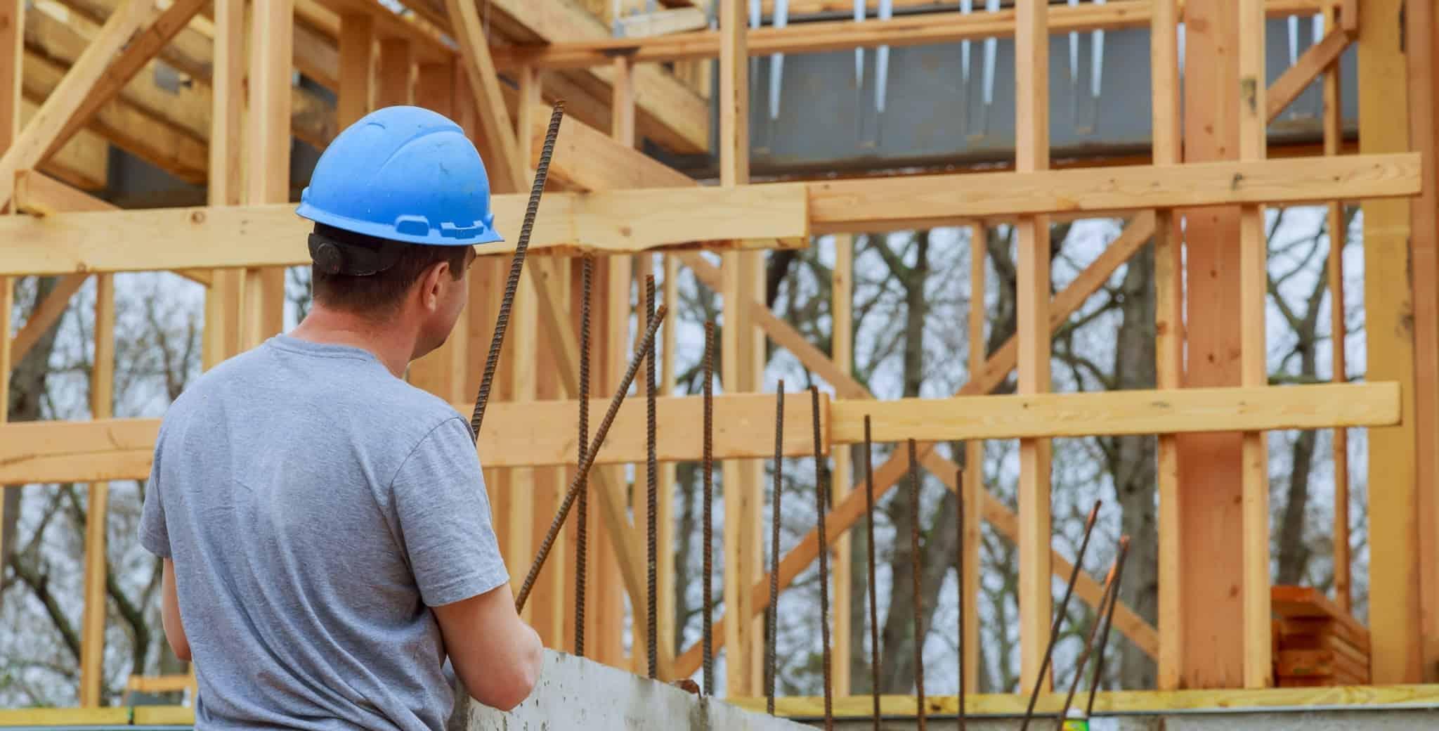 homem a construir uma habitação