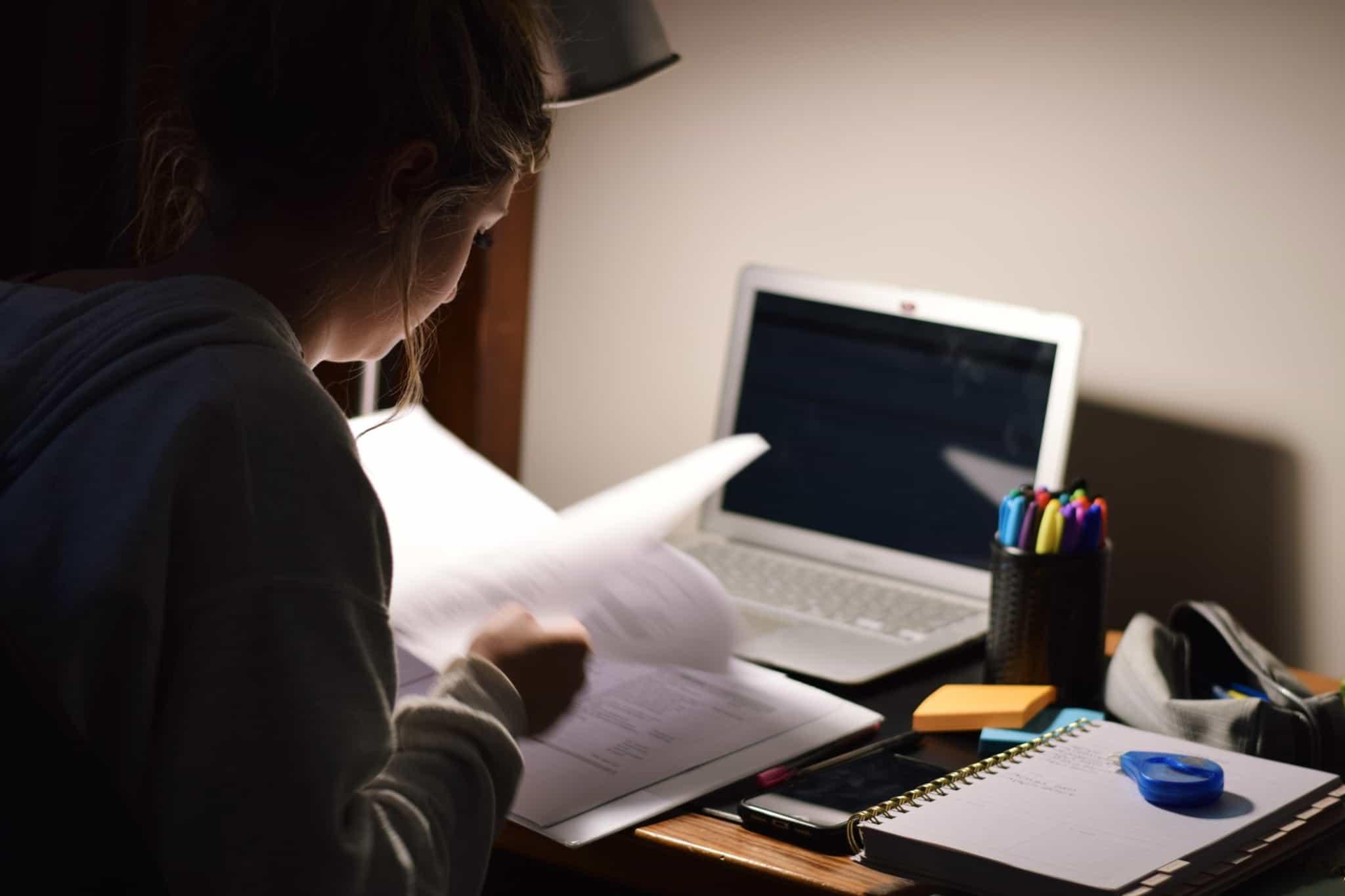 Jovem está a estudar, recorrendo a um livro e com o computador na sua frente