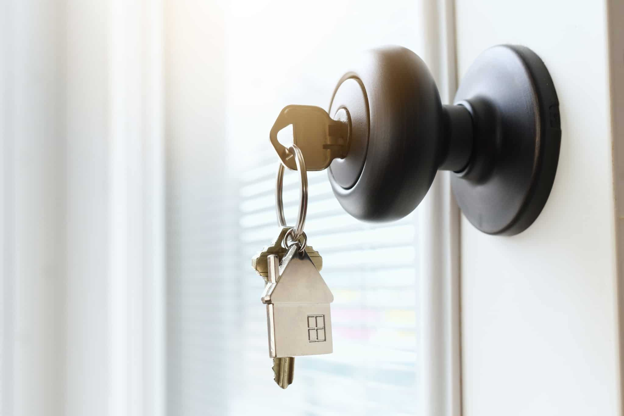 porta-chaves com uma casa em miniarura, pendurado com a cheve metida numa fechadura de uma porta branca.