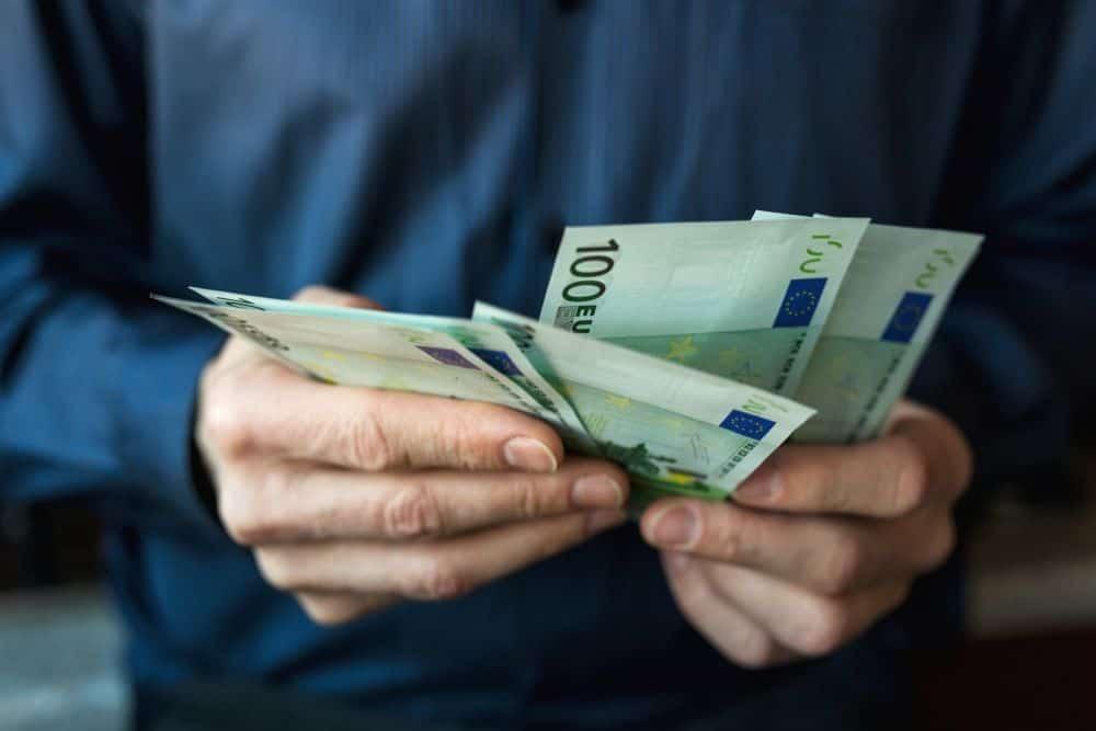 Mãos de homem com várias notas de 100 euros na mão a usar o subsídio de férias.