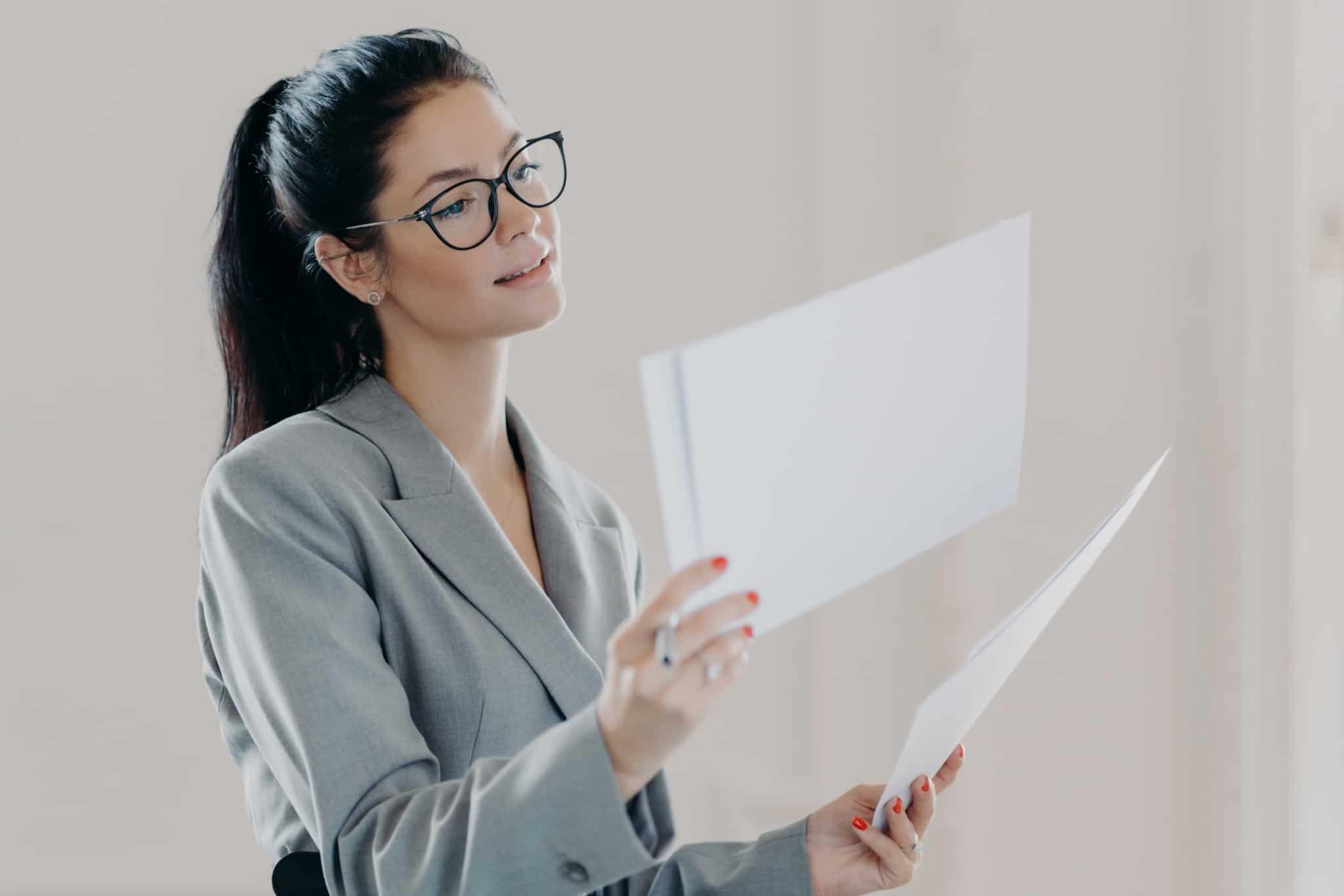Jovem mulher estuda e analisa documentos com propostas de crédito