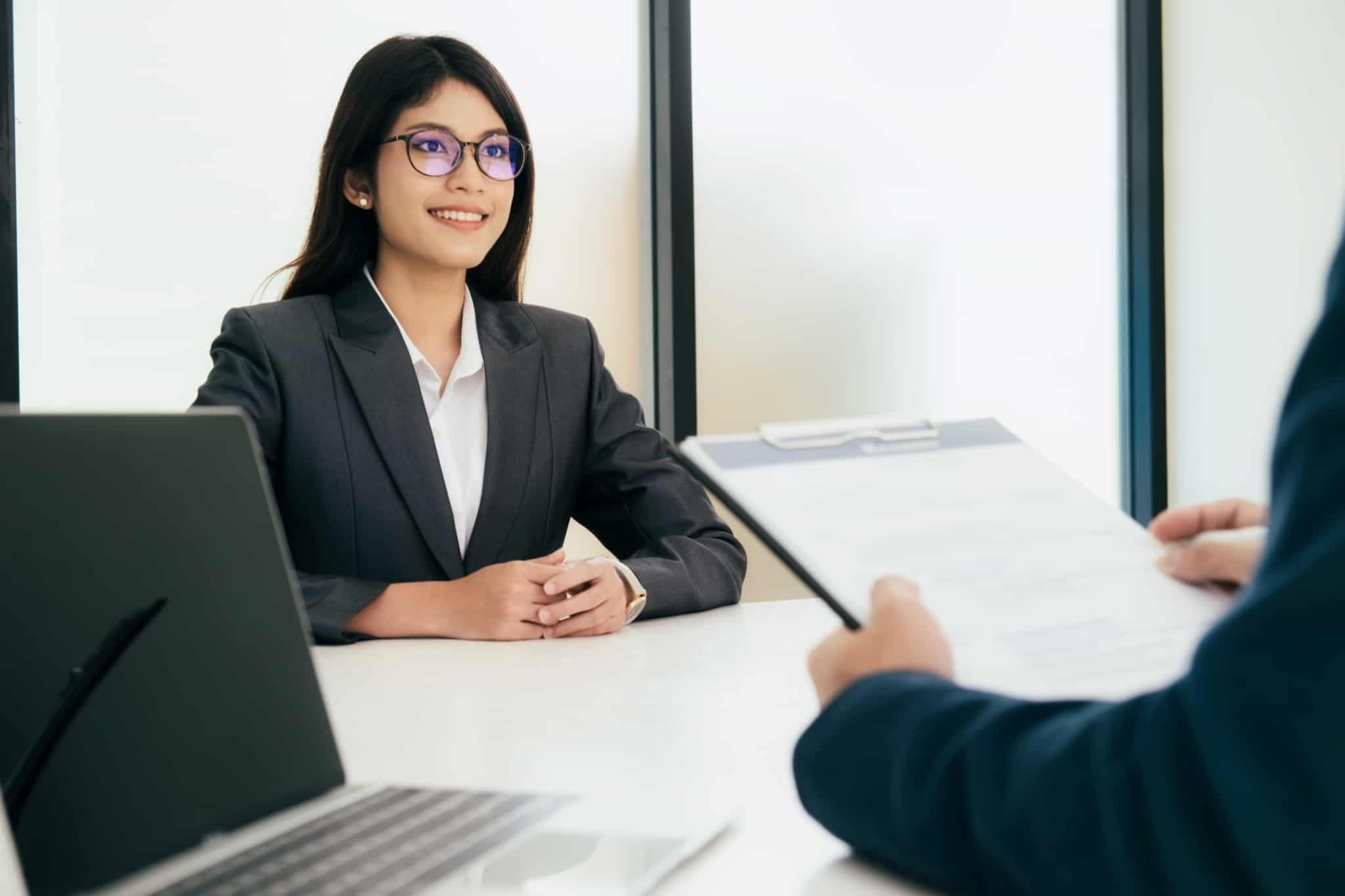 jovem mulher, recem licenciada, sorridente, confiante e com apresentação cuidada, na sua primeira entrevista de emprego