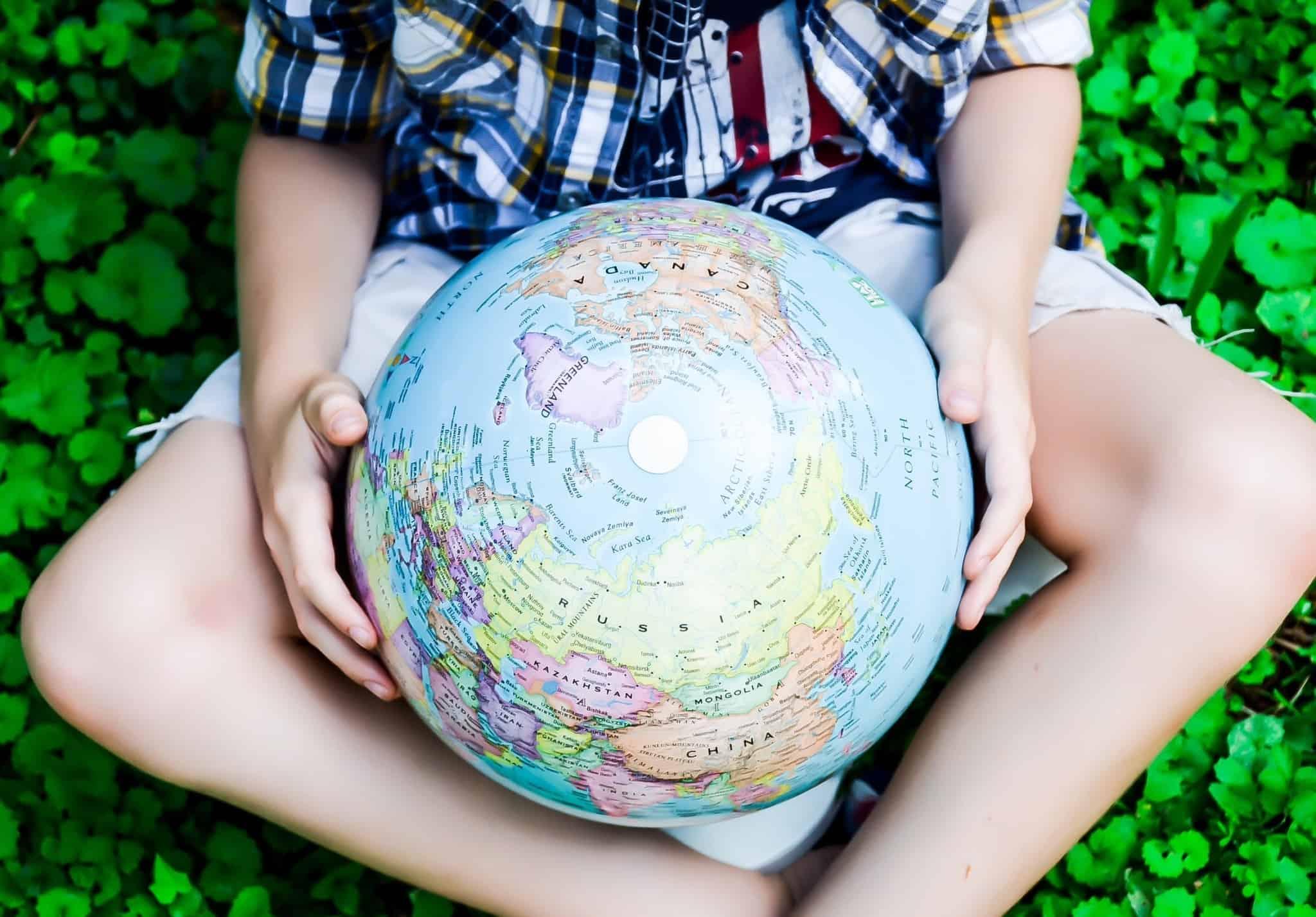jovem rapaz, sentado na relva bem verde, segura nas mãos, entre as pernas, um globo com o mapa mundo.