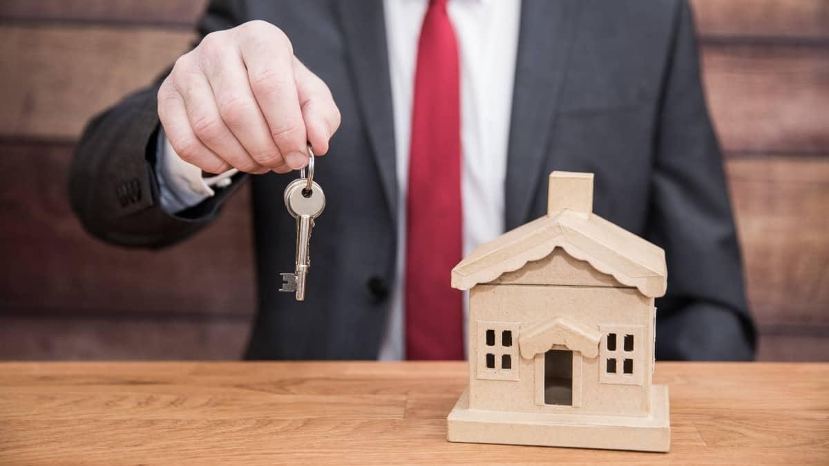 Homem de fato e gravata sentado a entregar uma chave com uma casa pequena de madeira em cima da mesa