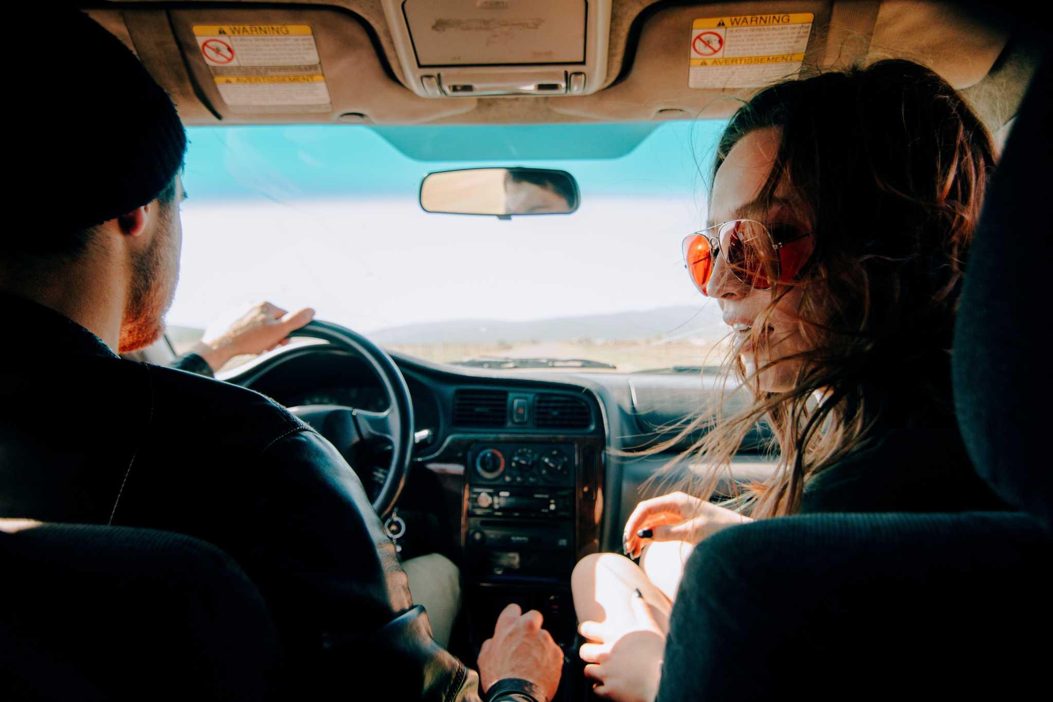 jobem casal, em viagem no seu automóvel, bem dispostos, a aproveitar a viagem