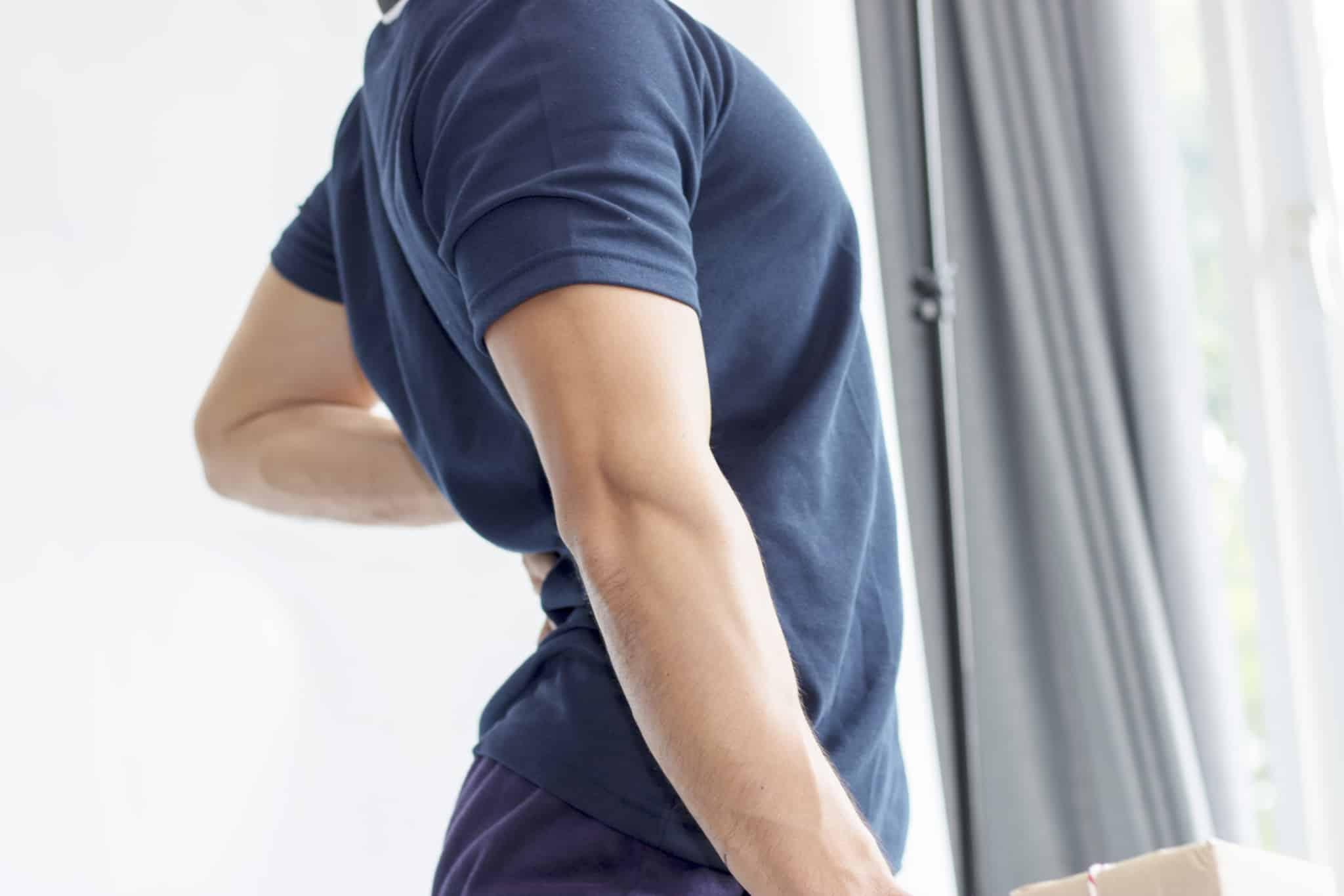 jovem homem, em pé junto a uma janela, tem a mão nas costas, na zona lombar, e o corpo contraído de dores, fruto de uma doença profissional que contraiu.