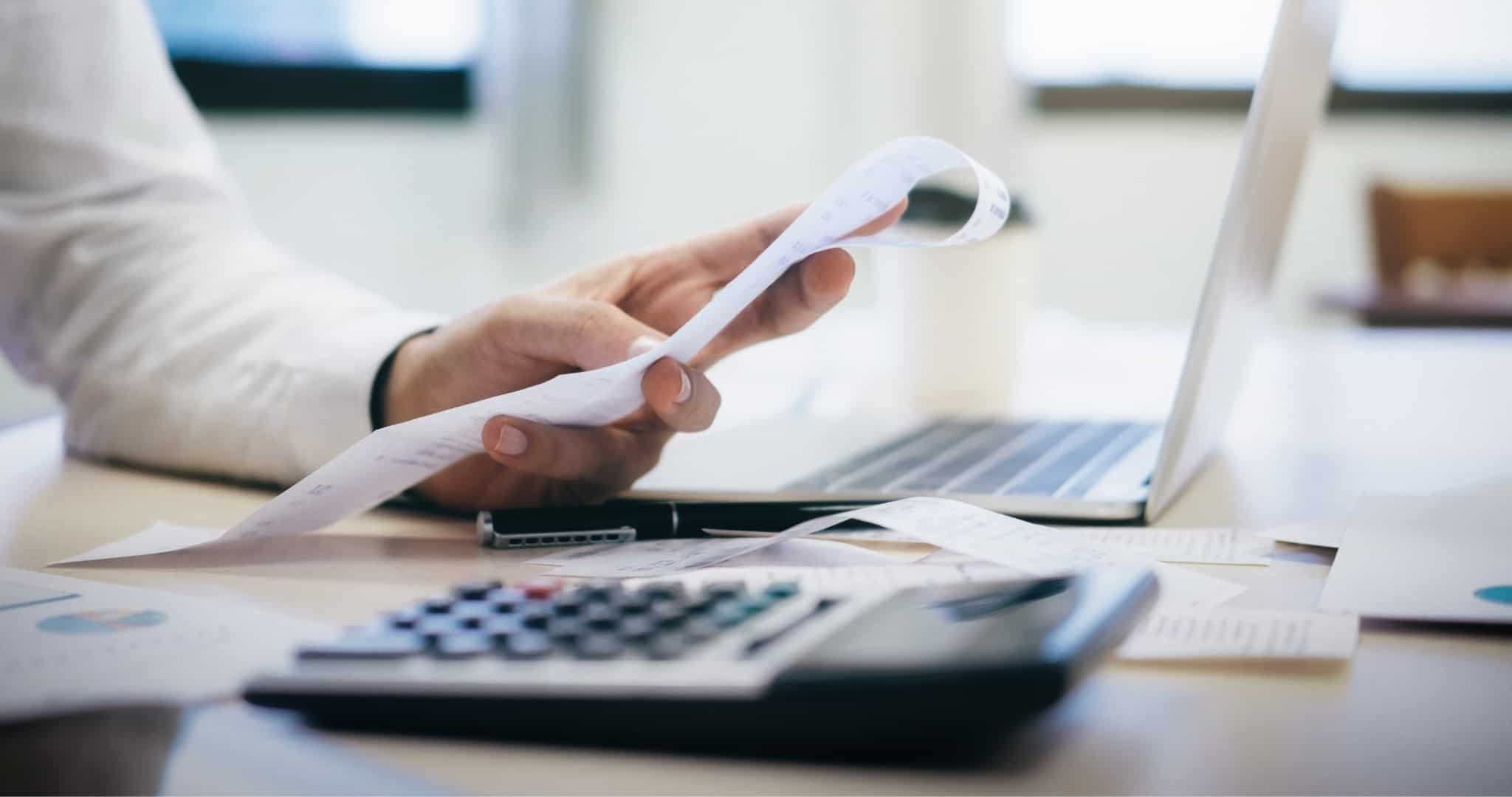 Mão de senhor a segurar um talão com uma calculadora e um portátil à frente a reequilibrar contas