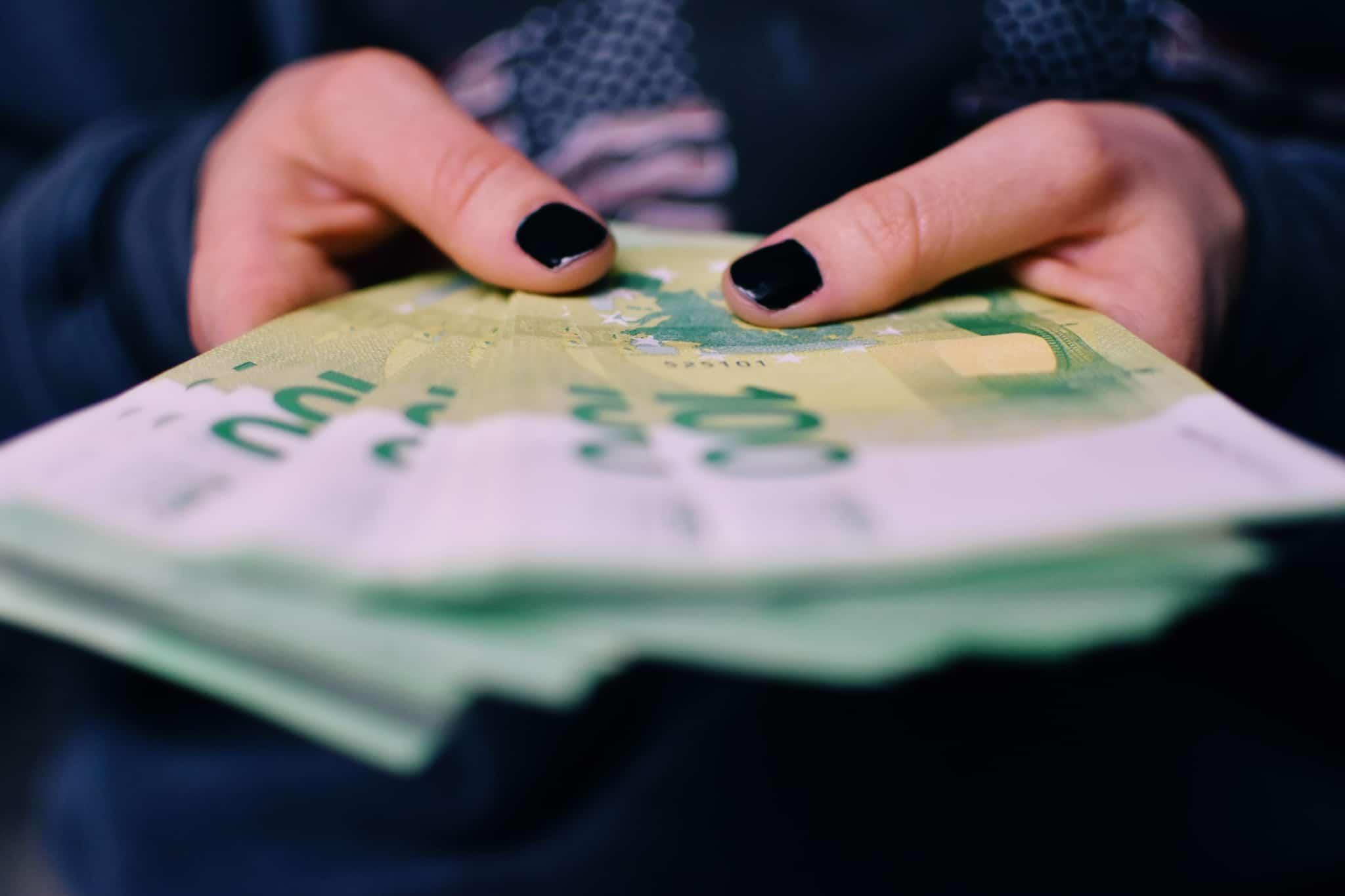 produção fotográfica que mostra as mãos de uma jovem mulher a segurar um moljo de notas de 100 euros, ilustra o pagamento em dinheiro (numerário)
